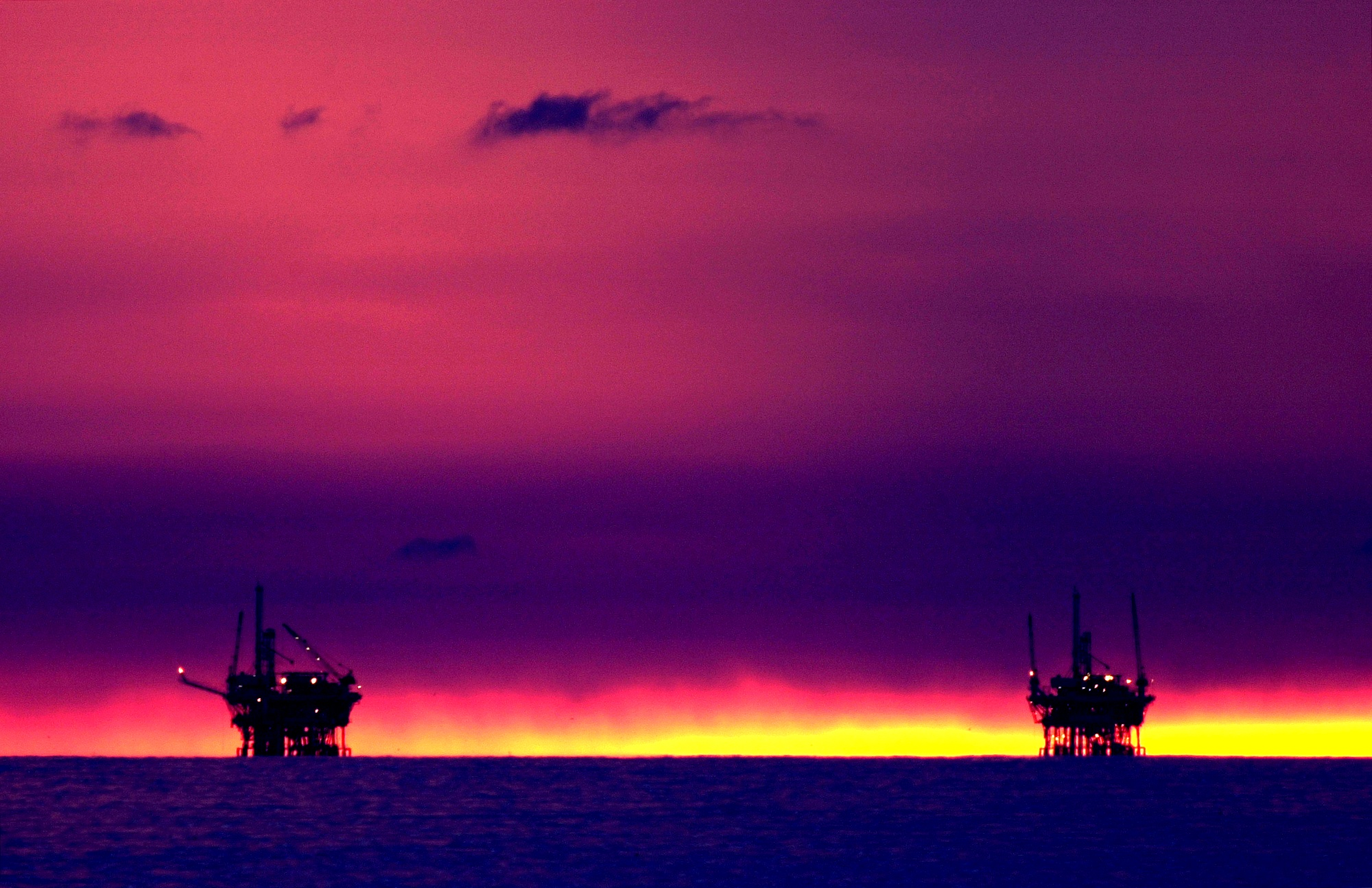 The sunset fades beyond the Hillhouse A, left, and Hillhouse B oil and gas platforms near the Federal Ecological Reserve in the Santa Barbara Channel near Santa Barbara, CA.