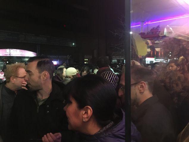 People watching Brooklyn Congresswoman Yvette Clarke's emergency meeting on President Trump's Muslim travel ban on a screen outside the Makki Mosque in Brooklyn.