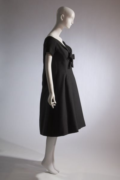 Black wool trapeze line dress; wide modified sweetheart neck with self bow; short kimono sleeves; below-knee length with soft flare; loosely shaped back; Dior; trapeze; The Museum at FIT