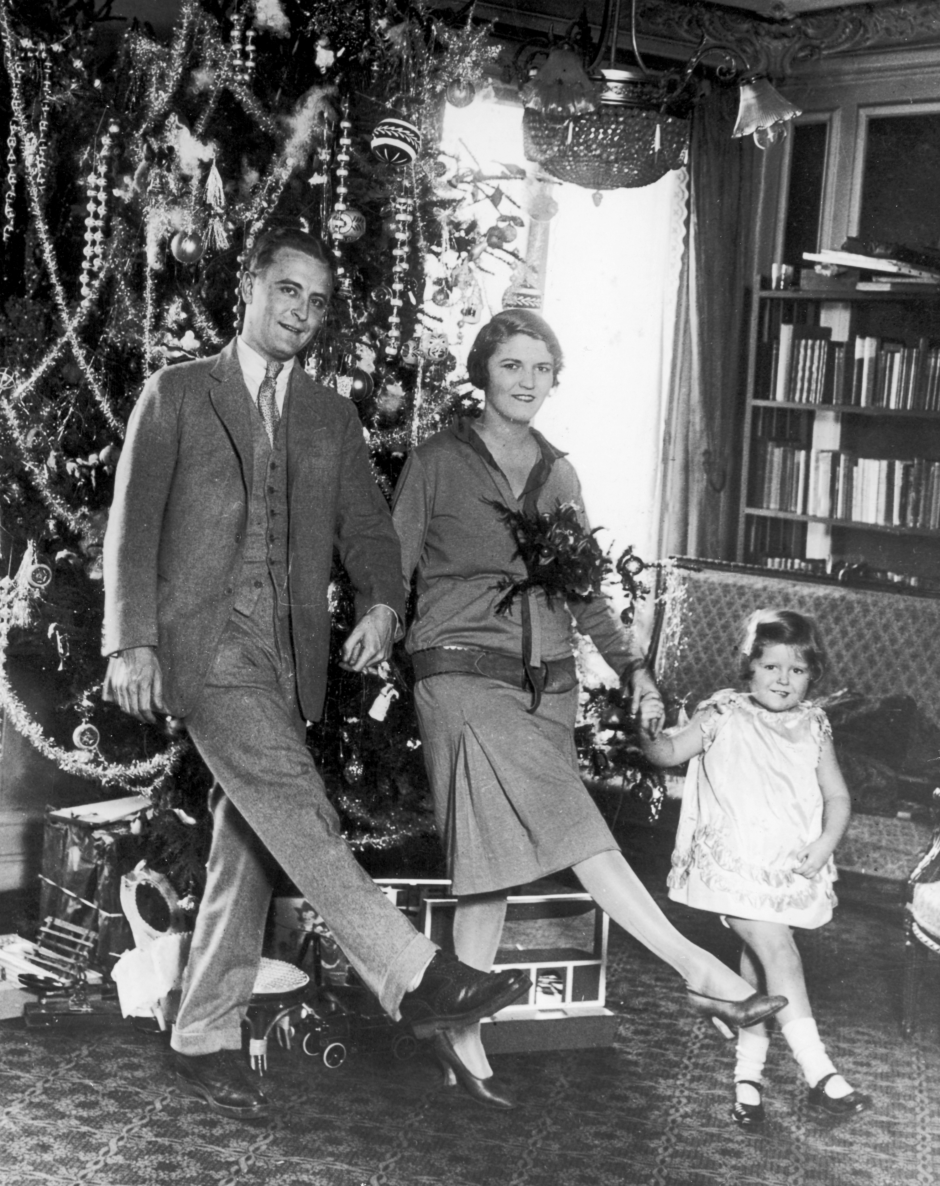 American author F Scott Fitzgerald (1896 - 1940) dances with his wife Zelda Fitzgerald (nee Sayre) (1900 - 1948) and daughter Frances (aka 'Scottie') in front of the Christmas tree in Paris. (Photo by Hulton Archive/Getty Images)