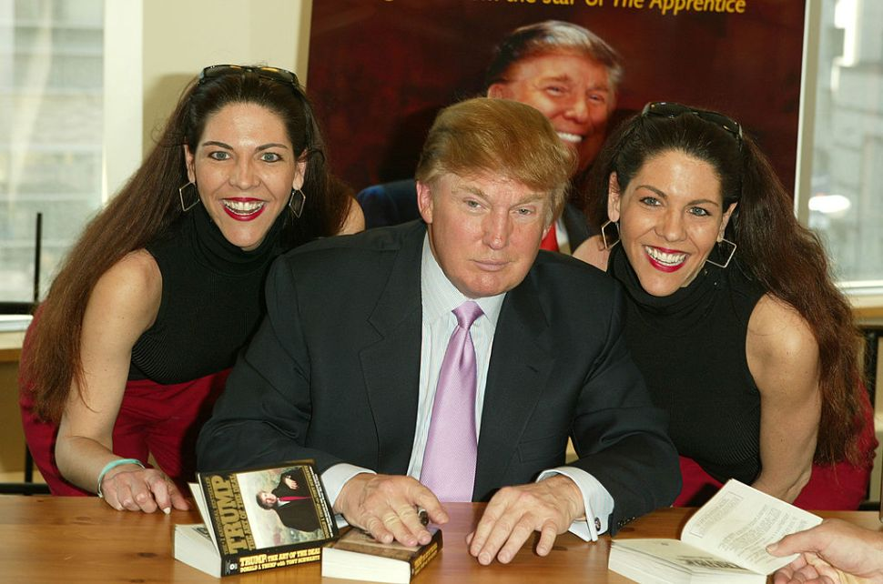 """NEW YORK - MARCH 24: Donald Trump poses for a picture with two fans while he signs copies of his new book """"How To Get Rich"""" March 24, 2004 at Barnes and Noble in Lincoln Center in New York City. (Photo by Peter Kramer/Getty Images)"""