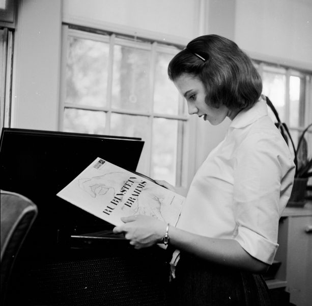 circa 1955: A teenage girl studying a record cover before playing the record inside it. (Photo by