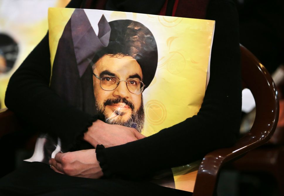 A Shiite supporter holds a poster showing Hassan Nasrallah, the head of Lebanon's militant Shiite Muslim movement Hezbollah, as he addresses supporters through a giant screen during a meeting in Beirut's southern suburb of Mujammaa Sayyed al-Shuhada on January 30, 2014. Hezbollah chief said he does not want war with Israel, after the Israeli military shelled border areas following a Hezbollah attack that left two Israeli soldiers dead. AFP PHOTO/JOSEPH EID