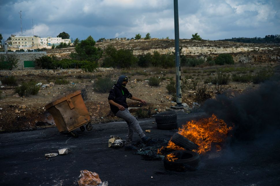BEIT-EL, WEST BANK - OCTOBER 08: Palestinian protester kicks over a pile of burning tires during clashes with IDF and Israeli Border Police on October 8, 2015 in Beit-El, West-Bank. As Tension rises between Israel and Palestine in the past weeks, many stabbing attack happen around Israel and Clashes between Israeli security forces and Palestinian youth.