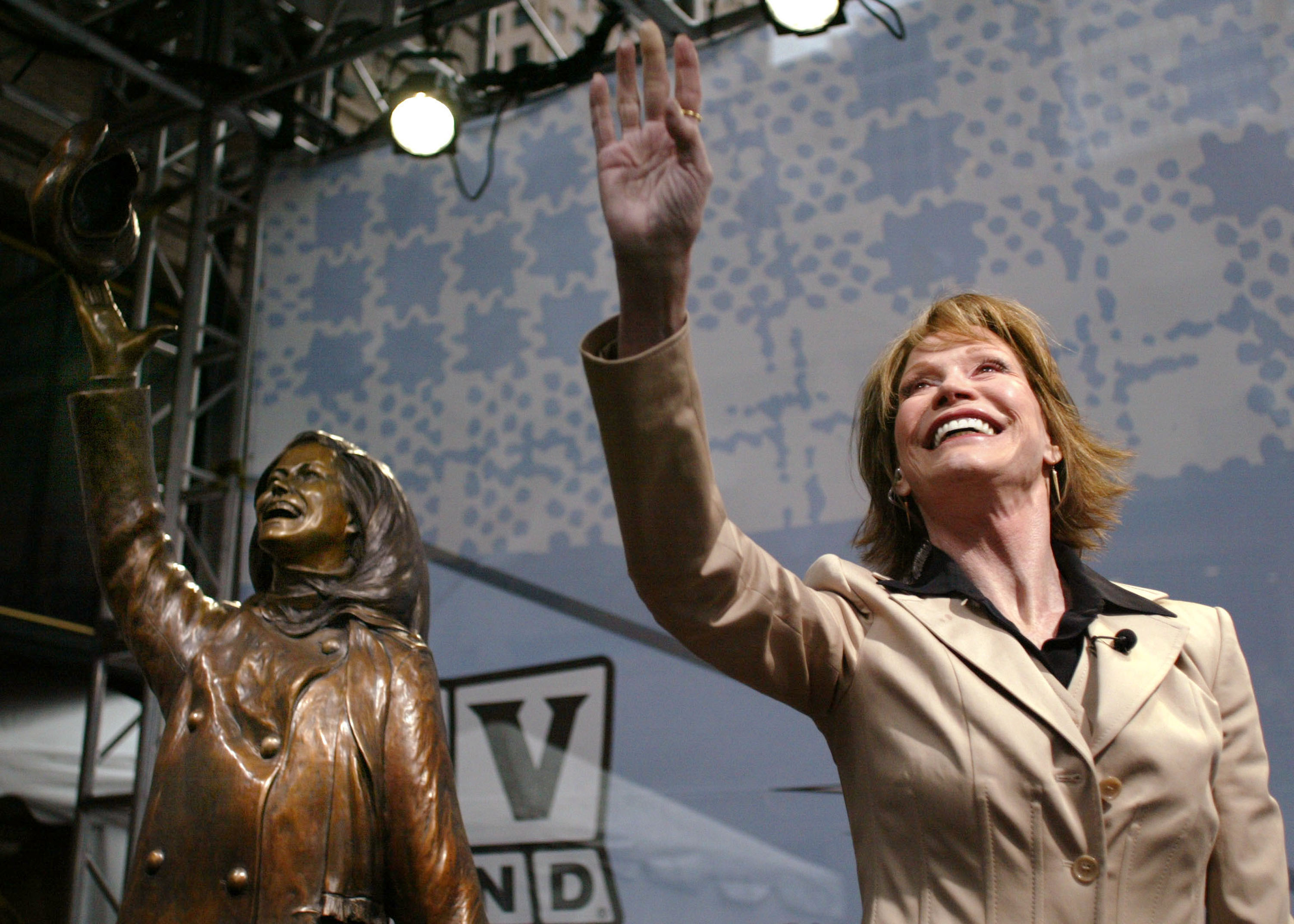 Mary Tyler Moore waves to the crowd next to a statue honoring her. The statue depicts Moore tossing her hat from the opening credits of The Mary Tyler Moore Show.