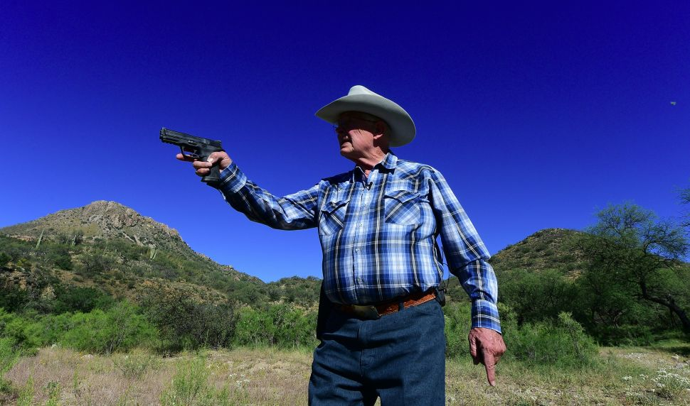 Jim Chilton carries his Smith and Wesson pistol for protection as he approaches the US-Mexico border at his ranch some 20 miles southeast of Arivaca, Arizona on October 14, 2016. Chilton owns a 50,000-acre (20234-hectare) cattle ranch where illegals but mostly drug packers have been crossing easily for many years. / AFP / Frederic J. BROWN