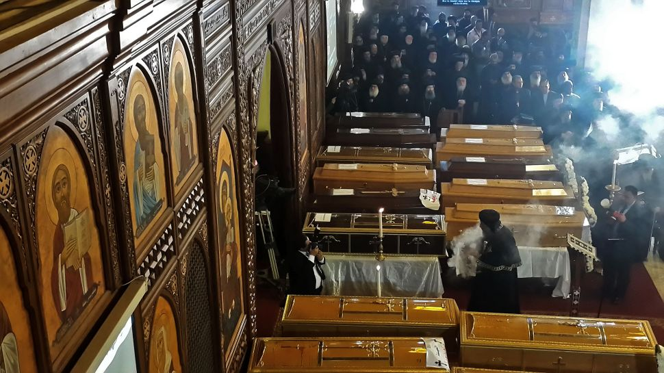 Egyptian clergymen stand next to the coffins of the victims.