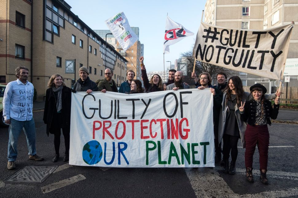 LONDON, ENGLAND - DECEMBER 22: Defendants pose behind a banner outside Ealing Magistrates Court before appearing on a charge of wilful obstruction after blocking a road near Heathrow Airport in protest at climate change on December 22, 2016 in London, England. 15 protesters were arrested in November after lying down and blocking a section of the M4 motorway to demonstrate against airport expansion and Heathrow's effect on climate change.