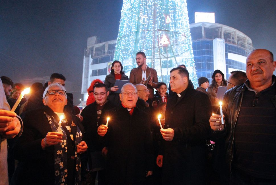 Iraqis gather at the al-Mansour square with Archbishop Louis Sako patriarch of the Chaldean Church in Iraq during Christmas and New Years eve celebrations in Baghdad on December 31, 2016.