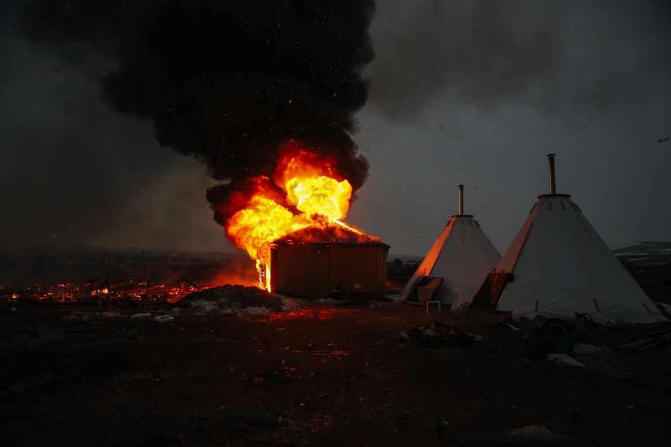 Campers set structures on fire in preparation of the deadline to leave the protest camp on February 22, 2017 in Cannon Ball, North Dakota.