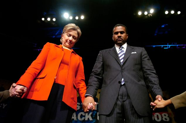 "Democratic presidential hopeful Sen. Hillary Clinton (D-NY) with television talk show host Tavis Smiley hold hands with members of the crowd at the ""State Of The Black Union"" symposium at the Ernest E. Morial Convention Center February 23, 2008 in New Orleans, Louisiana."