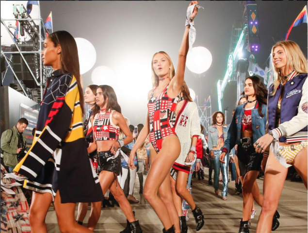 Models prepare to walk the runway at the Tommy x Gigi show in LA