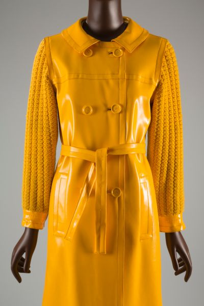 Double breasted coat in bright yellow vinyl plastic; open round neck with peter pan collar; plastic cuffs. Matching tie belt.