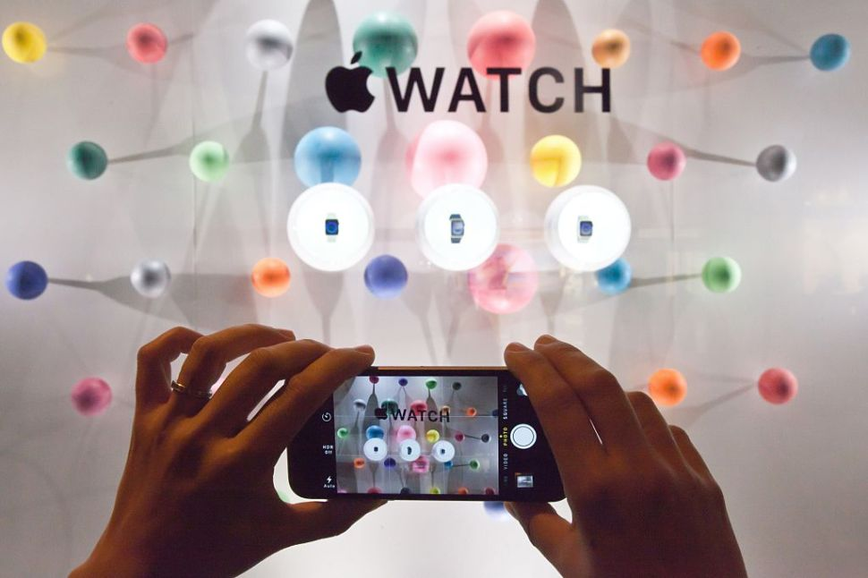 A woman photographs a window display of the Apple watch during the unveiling of the new and highly anticipated product at Saint-Honore street in Paris on September 30, 2014. AFP PHOTO / LOIC VENANCE (Photo credit should read LOIC VENANCE/AFP/Getty Images)