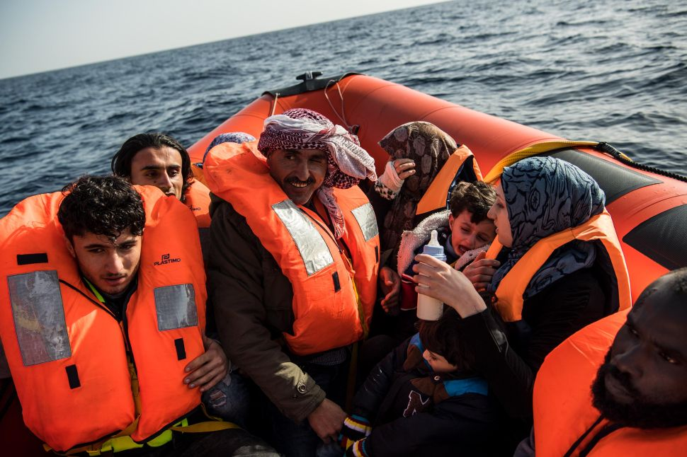 Syrian refugees are assisted by members of the Spanish NGO Proactiva Open Arms after being on board of a wooden boat sailing out of control 30 miles north of Libya on February 18, 2017.