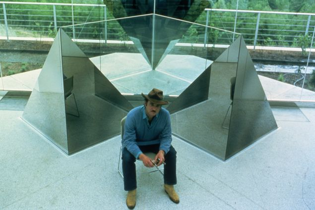 Larry Bell in front of an untitled sculpture from 1981.