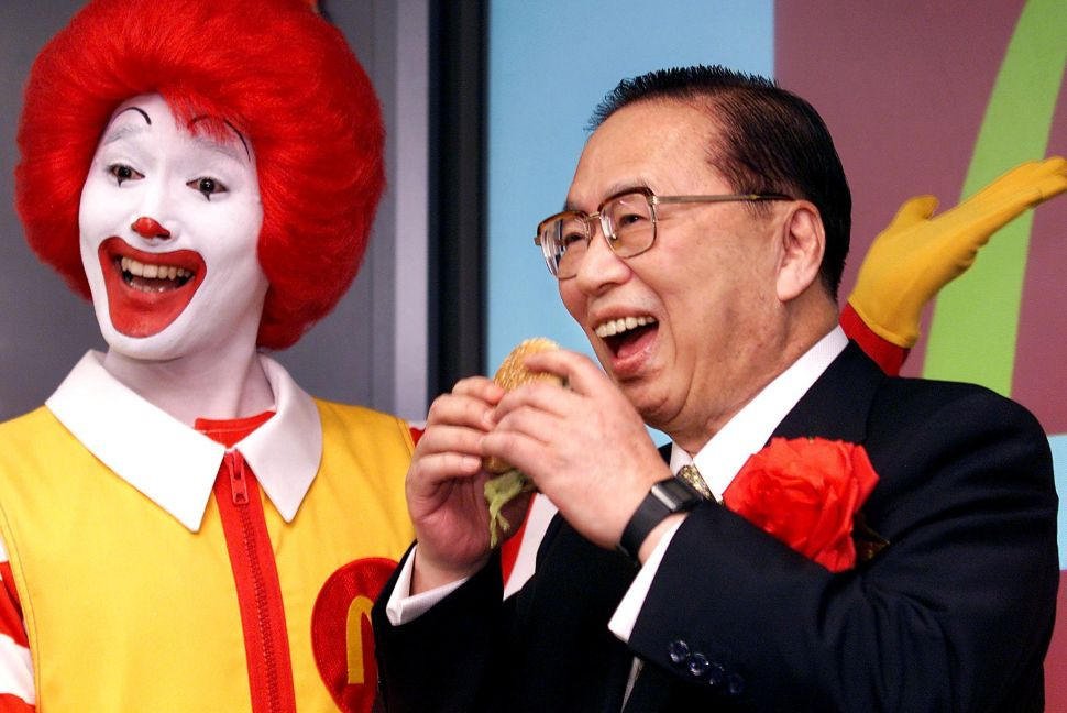 TOKYO, JAPAN: Fast food giant McDonald's (Japan) president, Den Fujita (R) bites into a BigMac as the company's stock is listed on the Jasdaq over-the-counter market in Tokyo, 26 July 2001, while McDonald's mascot Ronald (L) smiles. McDonald's shares were fixed at 4,700 yen (39.10 USD) on the first day of trading, compared to the initial public offer price of 4,300 yen (35.80 USD). AFP PHOTO/Yoshikazu TSUNO (Photo credit should read YOSHIKAZU TSUNO/AFP/Getty Images)