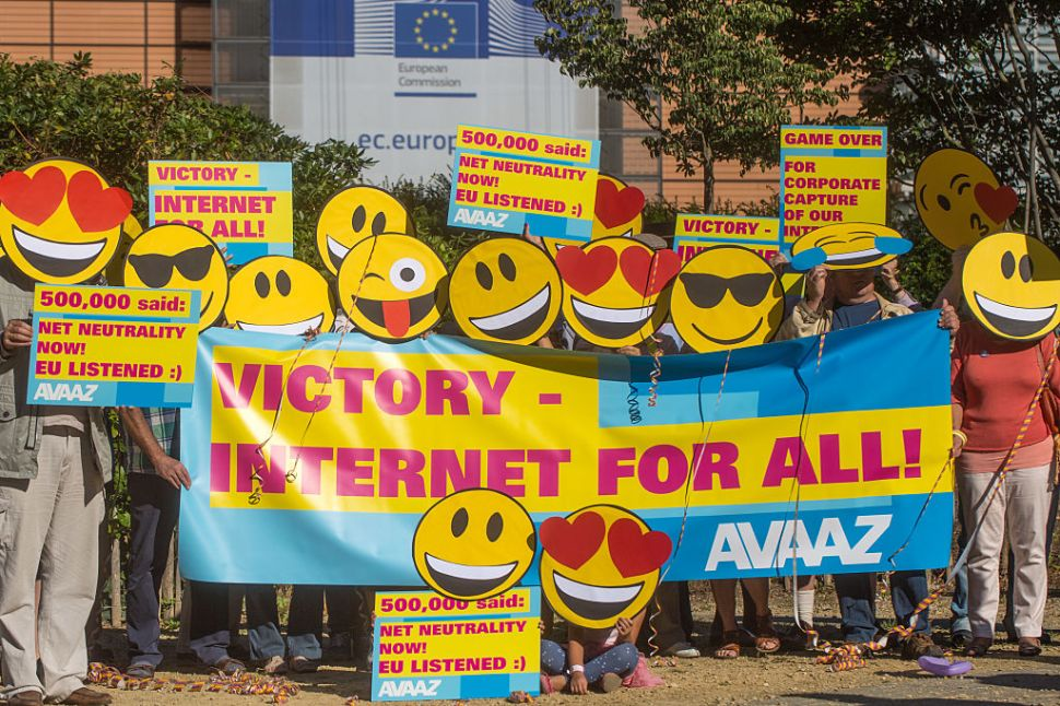 BRUSSELS, BELGIUM - AUGUST 30: Members of the global civic movement AVAAZ gather for a celebratory Emoji-flashmob by wearing masks with smiley emoji faces and posters that read 'Victory - Internet for all!' and 'Net Neutrality Now! EU listened' on August 30, 2016 in Brussels, Belgium. Europe introduced the first law in its history to protect internet democracy.