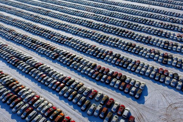 This aerial photo taken on January 16, 2017 shows new cars lined up at a parking lot in Shenyang, northeast China's Liaoning province. Auto sales in China, the world's biggest car market, surged at their fastest in three years in 2016, an industry group showed on January 12, jumping nearly 14 percent after authorities slashed a purchase tax. / AFP / STR / China OUT (Photo credit should read STR/AFP/Getty Images)