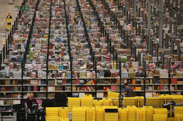 PETERBOROUGH, ENGLAND - NOVEMBER 28: Employees select and dispatch items in the huge Amazon 'fulfilment centre' warehouse on November 28, 2013 in Peterborough, England. The online retailer is preparing for 'Cyber Monday', as it predicts the busiest day for online shopping in the UK will fall on Monday December 2nd this year. On Cyber Monday in 2012 amazon.co.uk recorded over 3.5 million individual items ordered, which equates to 41 items purchased per second. The Peterborough fulfilment centre is 500,000 sq ft, equivalent to approximately seven football pitches in floor area. Amazon are due to employ more than 1,000 seasonal staff to cope with increased demand in the run up to Christmas. (Photo by Oli Scarff/Getty Images)