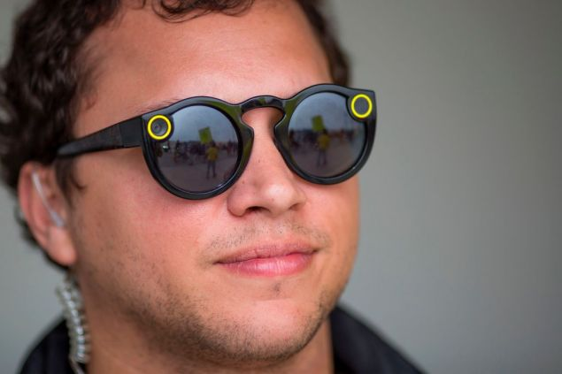 A resident demonstrating near a building converted into a Snap, Inc., vender of Spectacles sunglass cameras for Snapchat, on the Venice Beach boardwalk is reflected in a Spectacle worn by an employee on March 11, 2017 in the Venice area of Los Angeles, California. Protesters accuse Snap of buying up residential and small business buildings throughout Venice and adjacent Marina del Rey, then converting them into commercial offices as a kind of sprawling campus as part of the so-called Silicon Beach movement. / AFP PHOTO / DAVID MCNEW (Photo credit should read DAVID MCNEW/AFP/Getty Images)