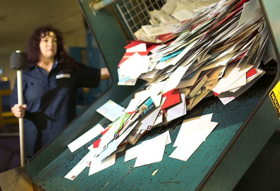 MIAMI, FL - DECEMBER 14: Susan Bird, a U.S. Postal Service mail handler, works to sort mail at a Processing and Distribution Center on the busiest mailing day of the year for the U.S. Postal Service on December 14, 2015 in Miami, Florida. With 10 days to go until Christmas eve, today the postal service was expecting 612 million pieces of mail to be sent, from first class letters to priority packages. (Photo by Joe Raedle/Getty Images)
