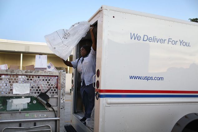MIAMI, FL - DECEMBER 14: Taquinnia Lee, a United States Postal Service mail handler, works to unload her mail truck at the Processing and Distribution Center after collecting mail on the busiest mailing day of the year for the U.S. Postal Service on December 14, 2015 in Miami, Florida. With 10 days to go until Christmas eve, today the postal service was expecting 612 million pieces of mail to be sent, from first class letters to priority packages. (Photo by Joe Raedle/Getty Images)