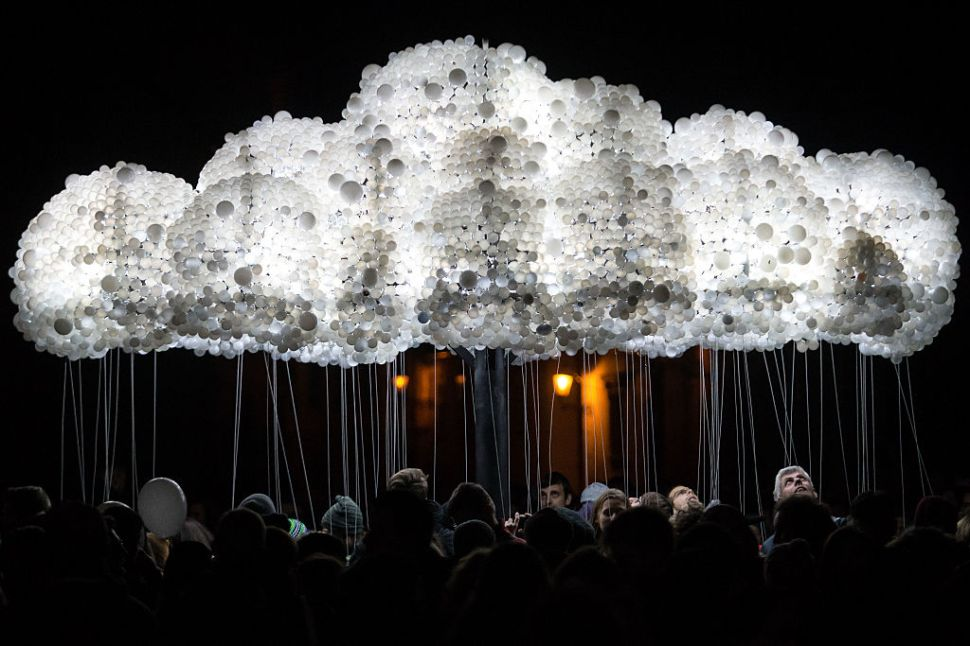 """People take part to an interactive art installation """"Cloud"""" created from 6,000 lightbulbs by Canadian artists Caitlind RC Brown & Wayne Garrett, during """"The White Night"""", a night-time art festival in Bratislava, Slovakia on October 08, 2016. / AFP / VLADIMIR SIMICEK (Photo credit should read VLADIMIR SIMICEK/AFP/Getty Images)"""