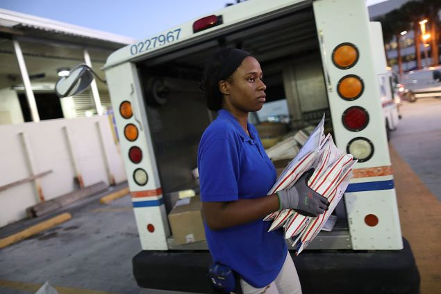 MIAMI, FL - DECEMBER 19: Debbie Kudehinbu, a U.S. Postal Service mail handler, unloads a mail truck at a Processing and Distribution Center on the busiest mailing day of the year for the U.S. Postal Service on December 19, 2016 in Miami, Florida. With 6 days to go until Christmas, today the postal service was expecting a crush of mail to be sent, from first class letters to priority packages. (Photo by Joe Raedle/Getty Images)