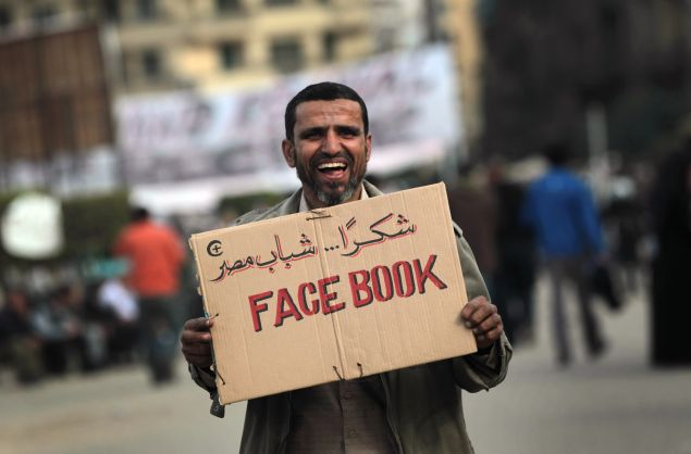 CAIRO, EGYPT - FEBRUARY 03: An anti-government demonstrator holds a sign during clashes on February 3, 2011 in Cairo, Egypt. Initial protests against the government were organized on internet social media. The Egyptian army positioned tanks between the protesters during a second day of violent skirmishes in and around Tahrir Square in Cairo. (Photo by John Moore/Getty Images)