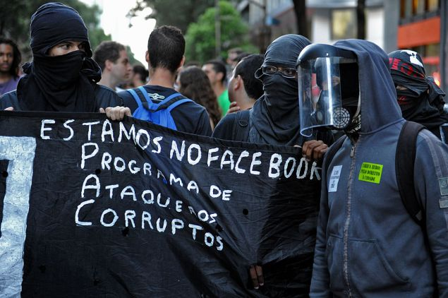 """Demonstrators take part in a protest against a public transport fare hike announced for January 2014 by Rio de Janeiro's Mayor Eduardo Paes, in the streets of the Brazilian city, on December 20, 2013. The banner reads """"We Are in Facebook: Programme of Attacks Against the Corrupt"""". AFP PHOTO/TASSO MARCELO (Photo credit should read TASSO MARCELO/AFP/Getty Images)"""