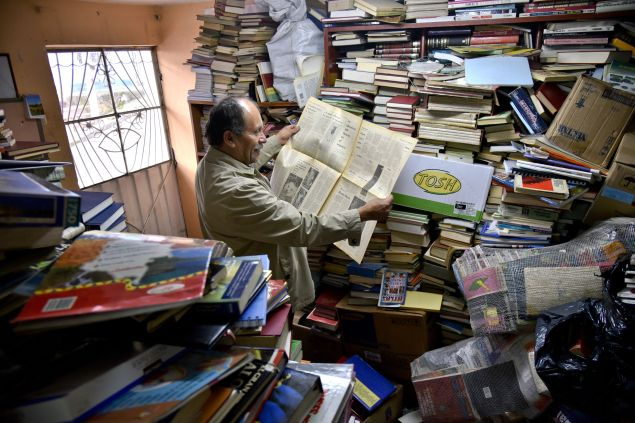 "Jose Alberto Gutierrez reads an old newspaper among books stacked in his library on the first floor of his house in Bogota, on May 18, 2017. Bogota has who rescues its books. For more than two decades Jose Alberto Gutierrez - ""The Lord of Books"", as he is known in Colombia - drives a garbage truck through the gray and cold streets of Bogota. In addition to wastes, he has collected thousands of books that crowded into his home, converted into a free library. / AFP PHOTO / GUILLERMO LEGARIA (Photo credit should read GUILLERMO LEGARIA/AFP/Getty Images)"