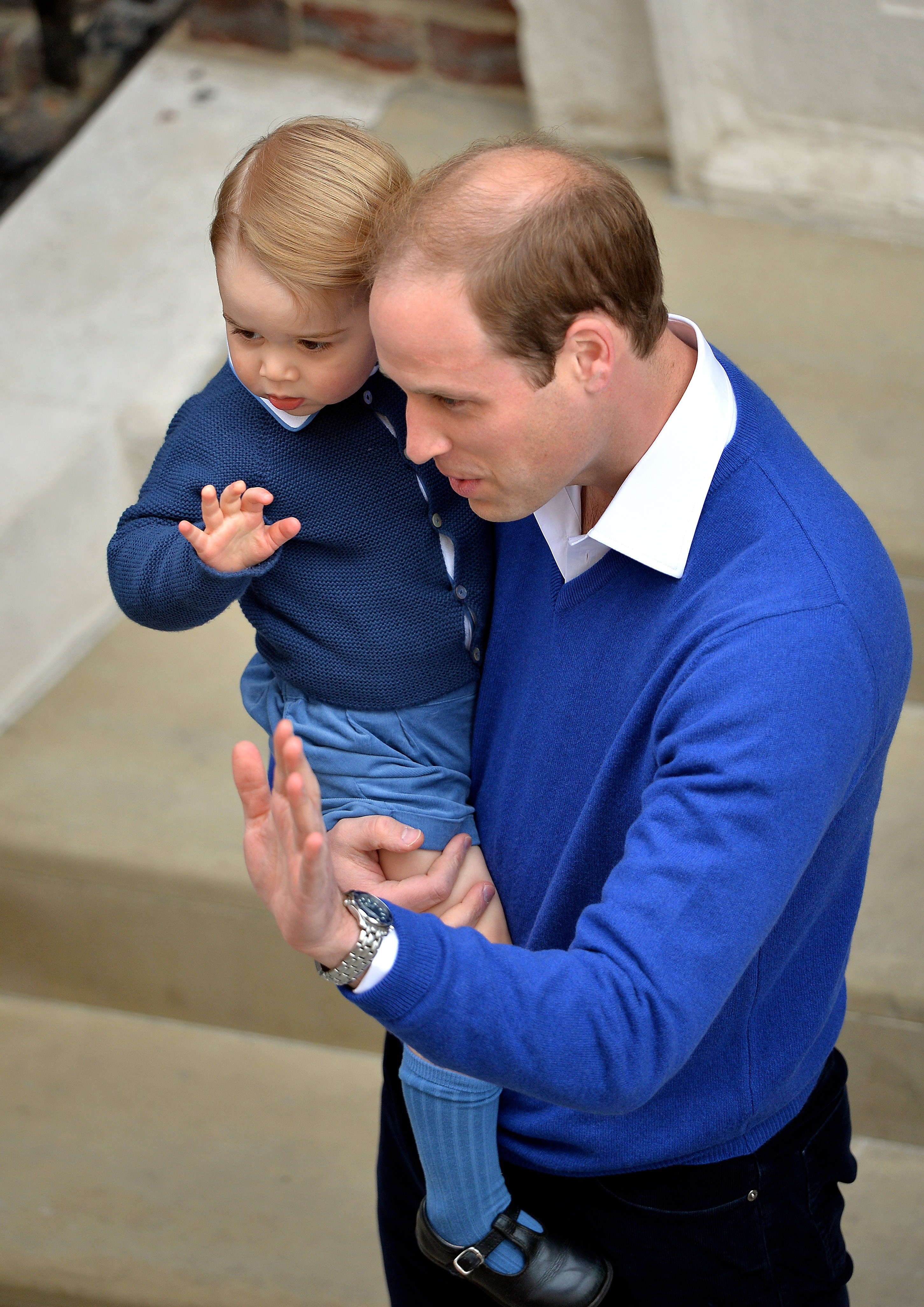 Britain's Prince William, Duke of Cambridge (R), and his son Prince George of Cambridge (L) wave as they return to the Lindo Wing at St Mary's Hospital in central London, on May 2, 2015 where his wife Catherine, Duchess of Cambridge, gave birth to their second child, a baby girl, earlier in the day. The Duchess of Cambridge was safely delivered of a daughter weighing 8lbs 3oz, Kensington Palace announced. The newly-born Princess of Cambridge is fourth in line to the British throne. AFP PHOTO / POOL / JOHN STILLWELL (Photo credit should read JOHN STILLWELL/AFP/Getty Images)