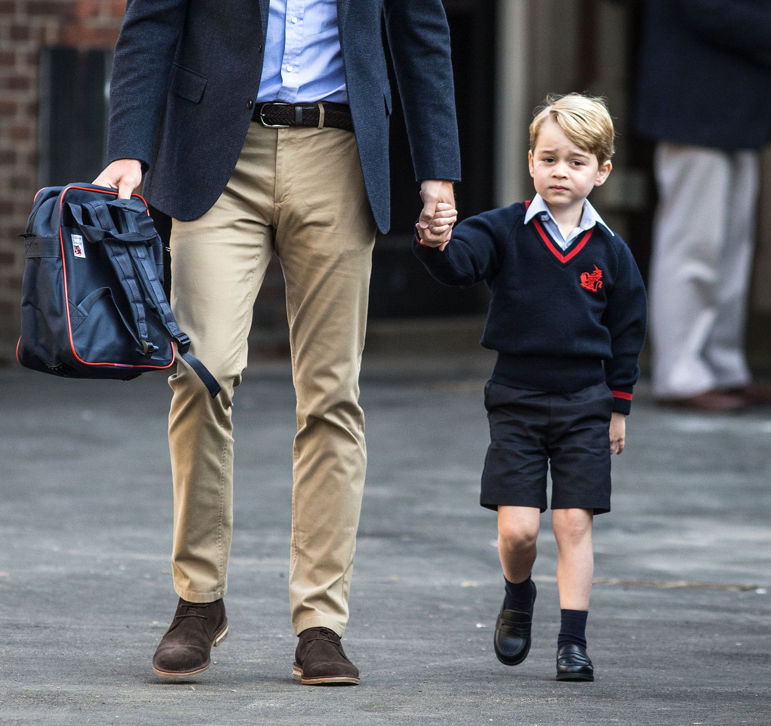 Britain's Prince George accompanied by Britain's Prince William, Duke of Cambridge arrives for his first day of school at Thomas's school on September 7, 2017 in southwest London. /