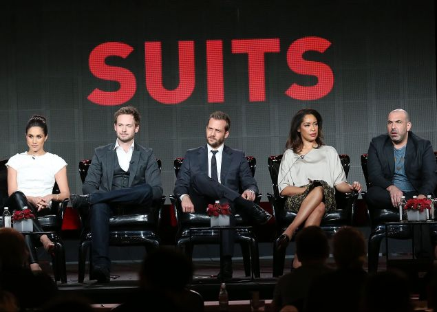 "PASADENA, CA - JANUARY 18: (L-R) Executive producer Aaron Korsh, actress Meghan Markle, actor Patrick J. Adams, actor Gabriel Macht, actress Gina Torres, actor Rick Hoffman, and actress Sarah Rafferty of the television show ""Suits"" speak during the NBC Universal portion of the 2014 Winter Television Critics Association Press Tour at the Langham Hotel on January 18, 2014 in Pasadena, California. (Photo by Frederick M. Brown/Getty Images)"
