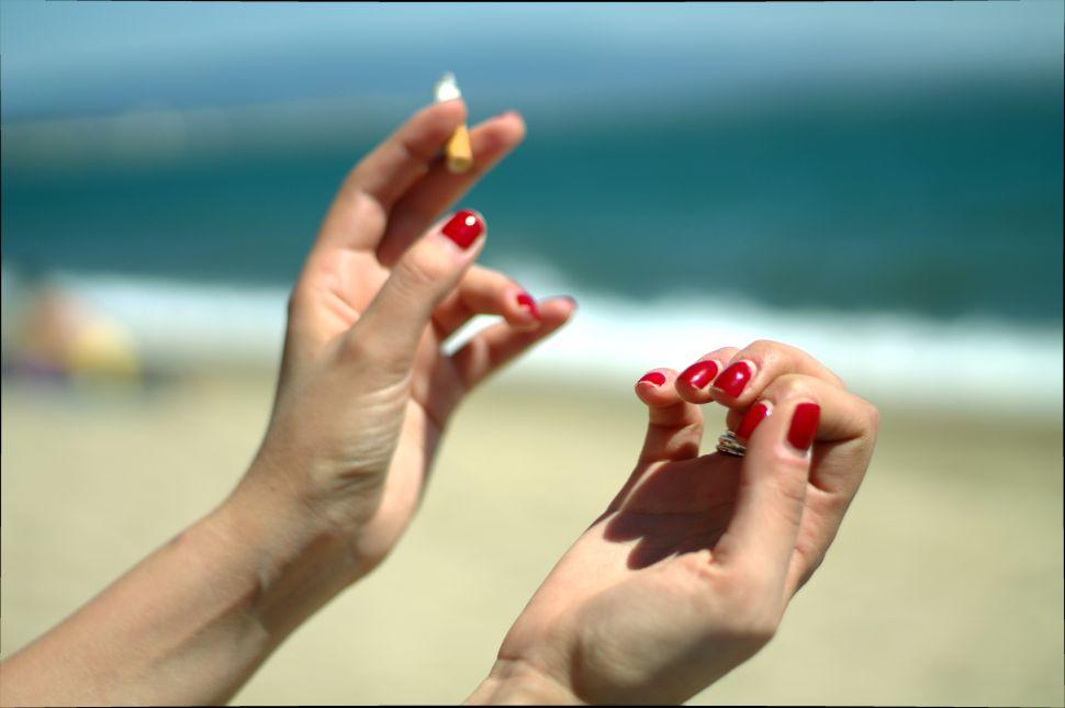 A woman smokes a cigarette on the beach.