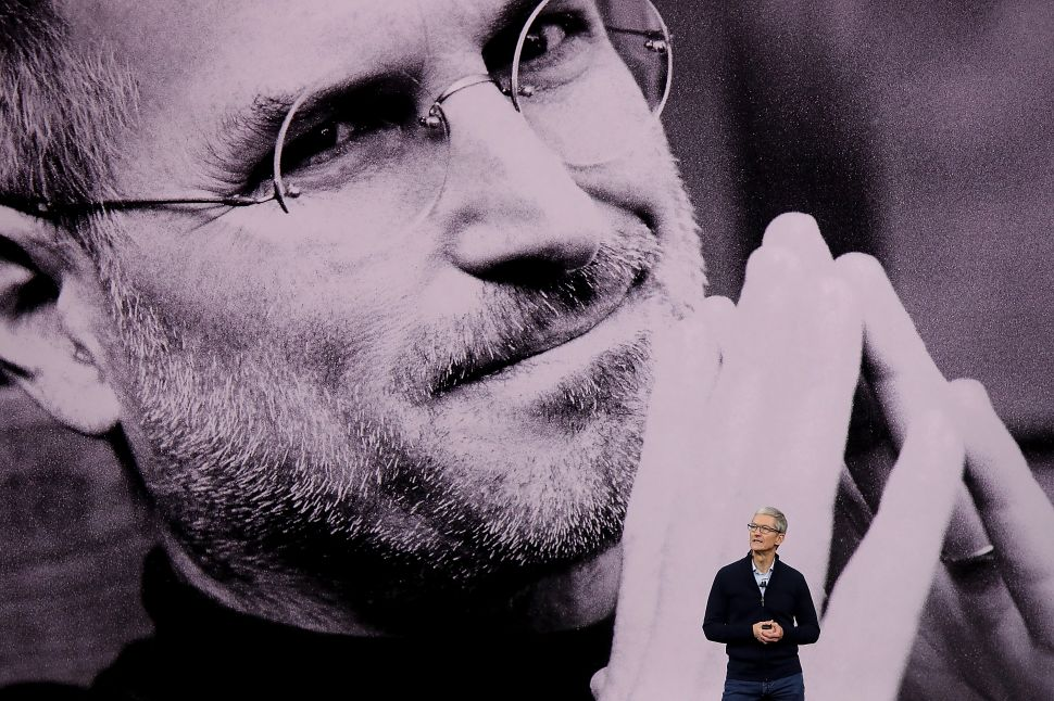Tim Cook stands in front of a keynote photo of Steve Jobs at an Apple launch event.