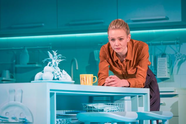 Carey Mulligan leans on a kitchen counter against a blue background in the off-broadway playGirls and Boys.