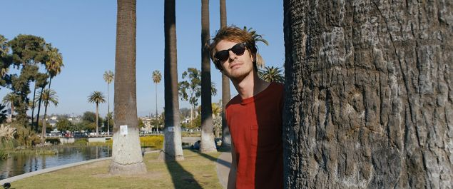 Andrew Garfield snoops around a tree in the movie Under the Silver Lake.