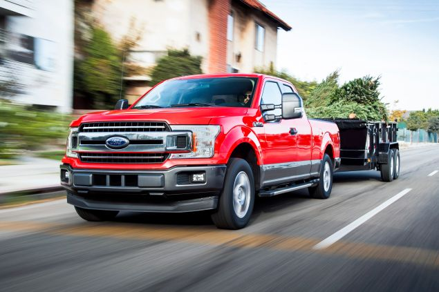 A red 2018 Ford F-150 tows a trailer full of Christmas trees.