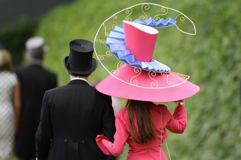 ASCOT, ENGLAND - JUNE 16: Racegoers walk by the racecourse on Ladies Day at Royal Ascot on June 16, 2011 in Ascot, England. The five-day meeting is one of the highlights of the horse racing calendar, with 2011 marking the 300th anniversary of the annual event. Horse racing has been held at the famous Berkshire course since 1711.