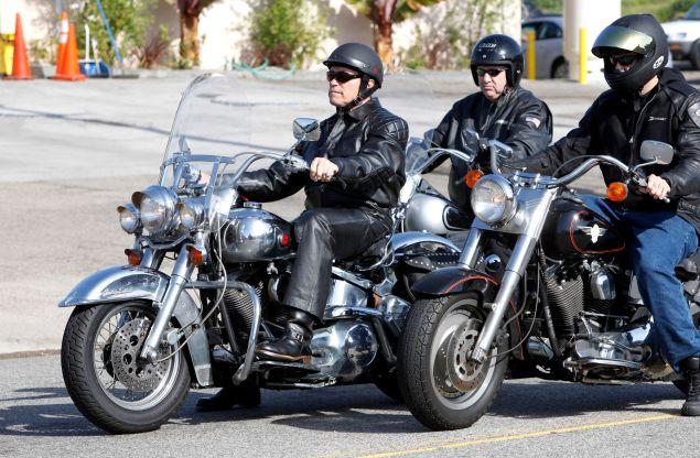 Arnold Schwarzenegger takes a ride on his all chrome Harley-Davidson.