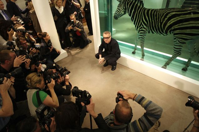 British artist Damien Hirst poses for photographs before his 2008 of more than 200 of his own works.