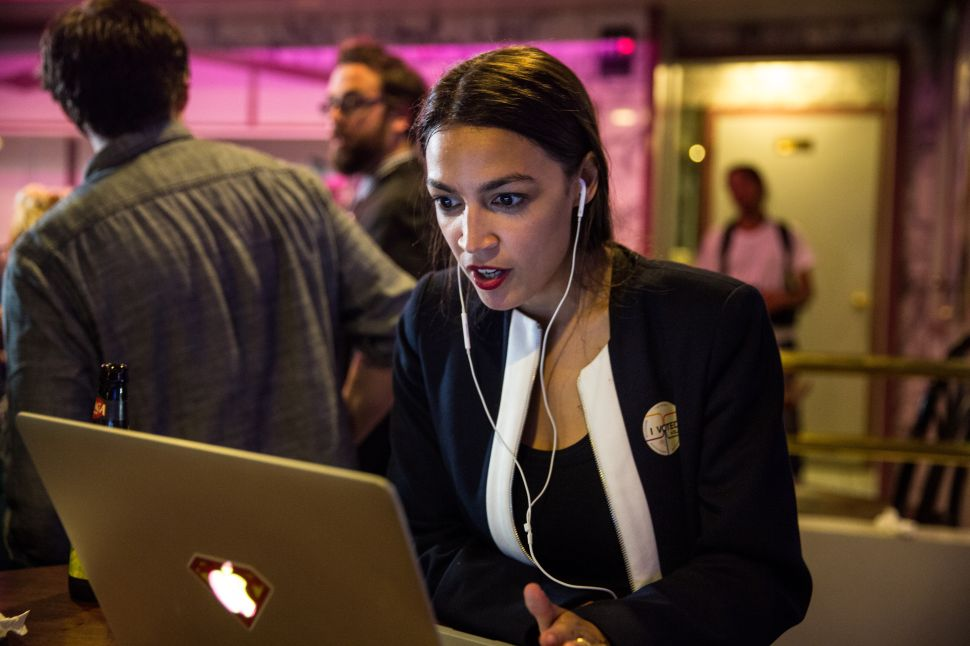 Alexandria Ocasio-Cortez works on a (hopefully secure) laptop during her victory party.
