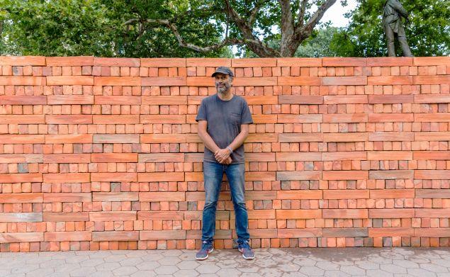 Bosco Sodi with his artwork made entirely of bricks, titled Muro.