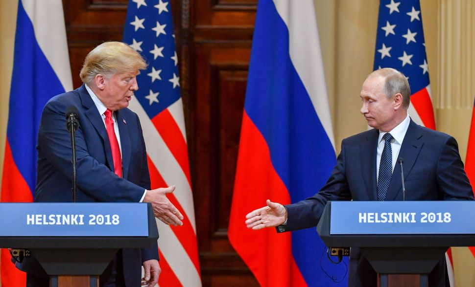 U.S. President Donald Trump (L) and Russia's President Vladimir Putin reach out to shake hands before attending a joint press conference after a meeting at the Presidential Palace in Helsinki, on July 16, 2018.