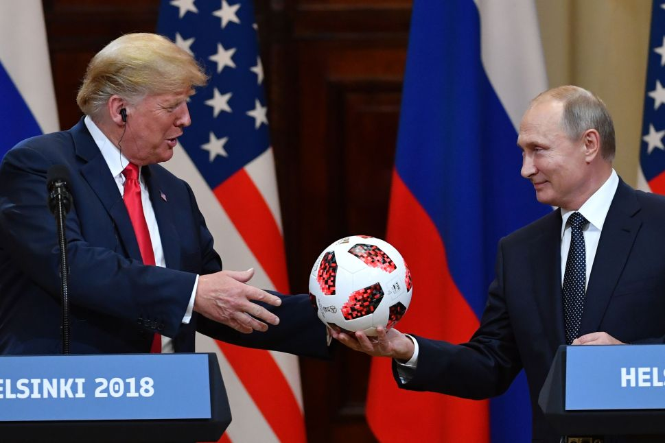 Russia's President Vladimir Putin (R) offers a ball from the 2018 football World Cup to U.S. President Donald Trump during a joint press conference after a meeting at the Presidential Palace in Helsinki.