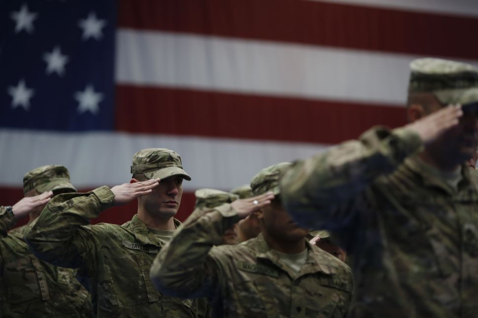 FORT KNOX, KY - FEBRUARY 27: Soldiers from the U.S. Army's 3rd Brigade Combat Team, 1st Infantry Division, salute during the playing of the Star Spangled Banner during a homecoming ceremony in the Natcher Physical Fitness Center on Fort Knox on February 27, 2014 in Fort Knox, Kentucky. About 100 soldiers returned to Fort Knox after a nine-month combat deployment conducting village stability operations and working alongside Afghan military and police forces. (Photo by Luke Sharrett/Getty Images)