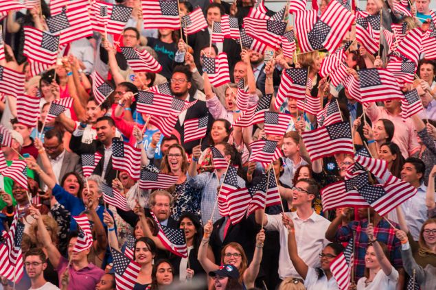People wave American flags at a primary night rally for Democratic presidential candidate Hillary Clinton in the Brooklyn Navy Yard, June 7, 2016 in Brooklyn, New York. Clinton will become the first woman in U.S. history to secure the presidential nomination of one of the country's two major political parties.