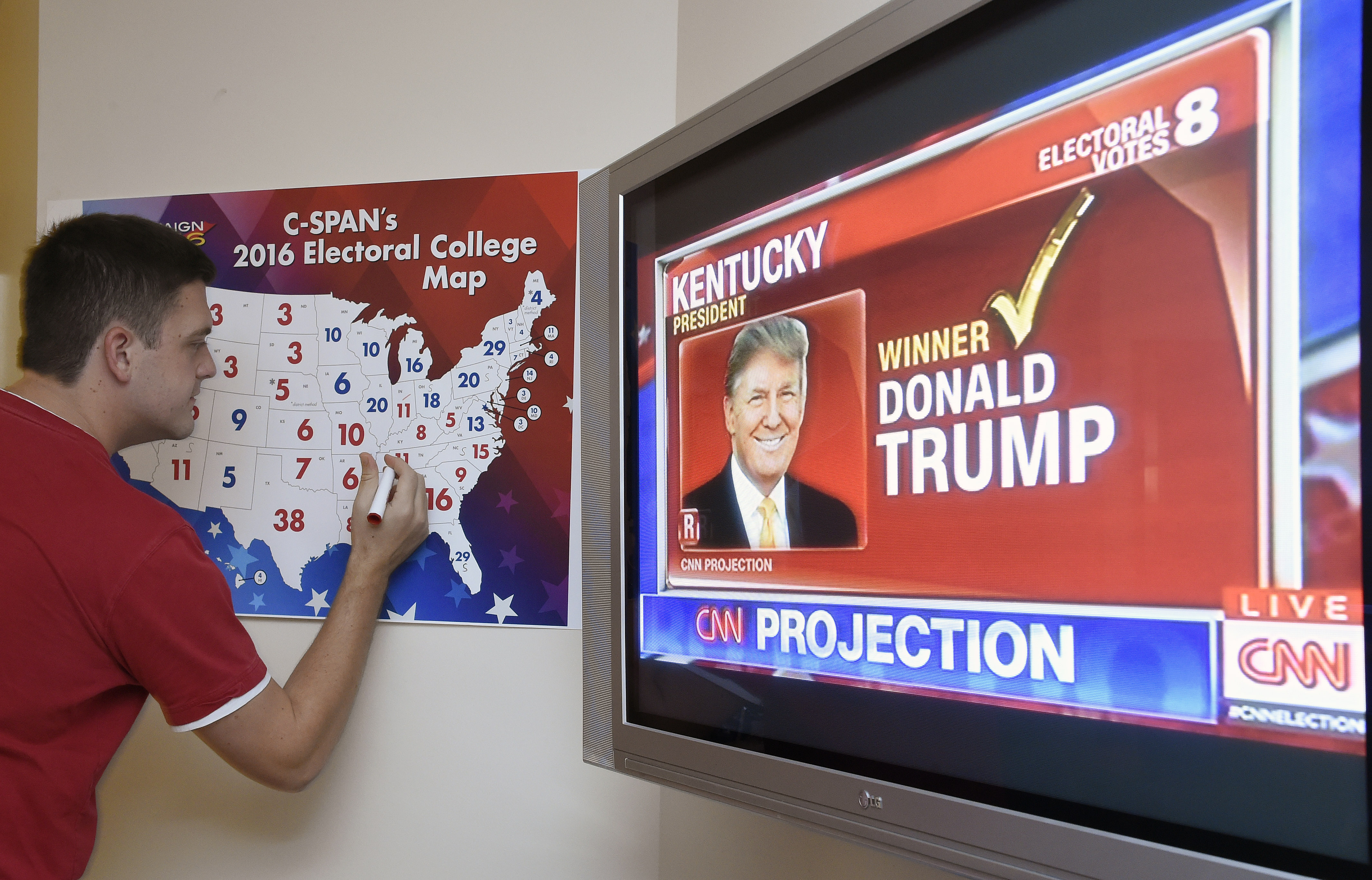 An electoral map is colored as states are projected for Donald Trump at an election watching party in Coconut Grove, Florida.